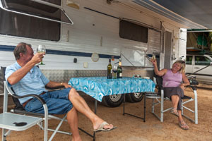 Retired couple sitting under awning of a large caravan toasting